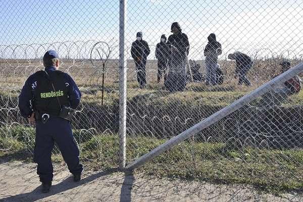 menekült és rendőr a kerítésnél